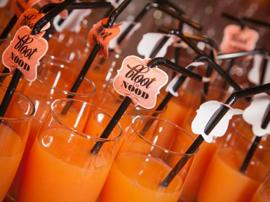 aperitief vruchtensap met versierde rietjes die gelabeld zijn met 'bloot nood'
